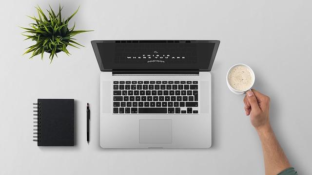 Ruka s kávou a laptop